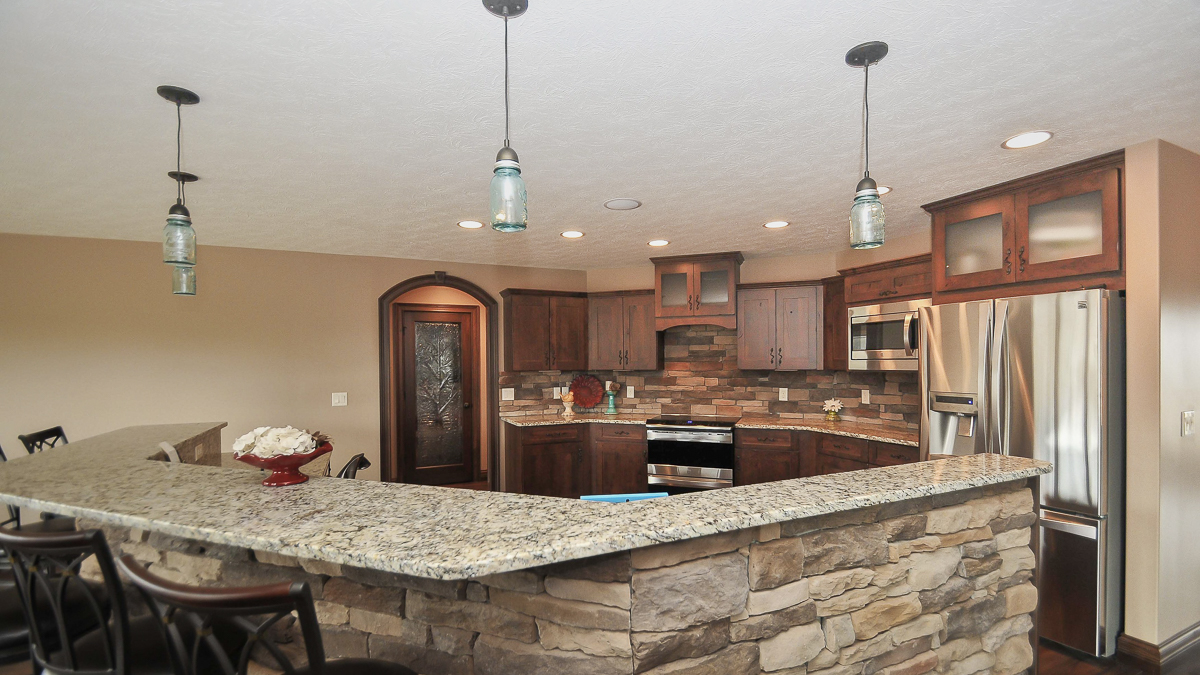 Kitchen of custom built home feautures stone backsplash, granite countertops and rustic wood stained cabinets