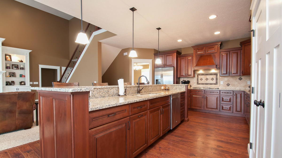 Kitchen of modified Belmont model features medium stained cabinets, granite countertops and travertine backsplash
