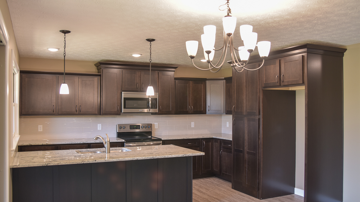 Kitchen of Avondale model features Echelon maple cabinets )Norwich in Truffle) and and walk in pantry disguised as a cabinet door! Granite countertops and subway backsplash