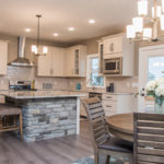 Kitchen of Windmill model features Echelon maple Addison with slab drawer in Latte, River White Granite, and subway backsplash