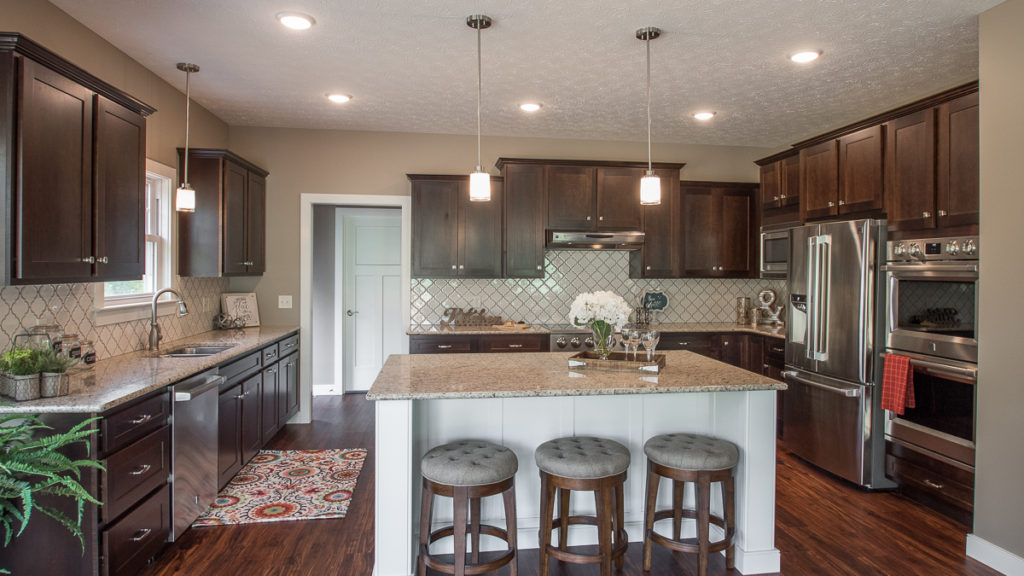 Kitchen of custom built home features Echelon Maple Norwich Linen for island only. Norwich Espresso for the rest of kitchen. Giallo Ornamental granite and decorative backsplash