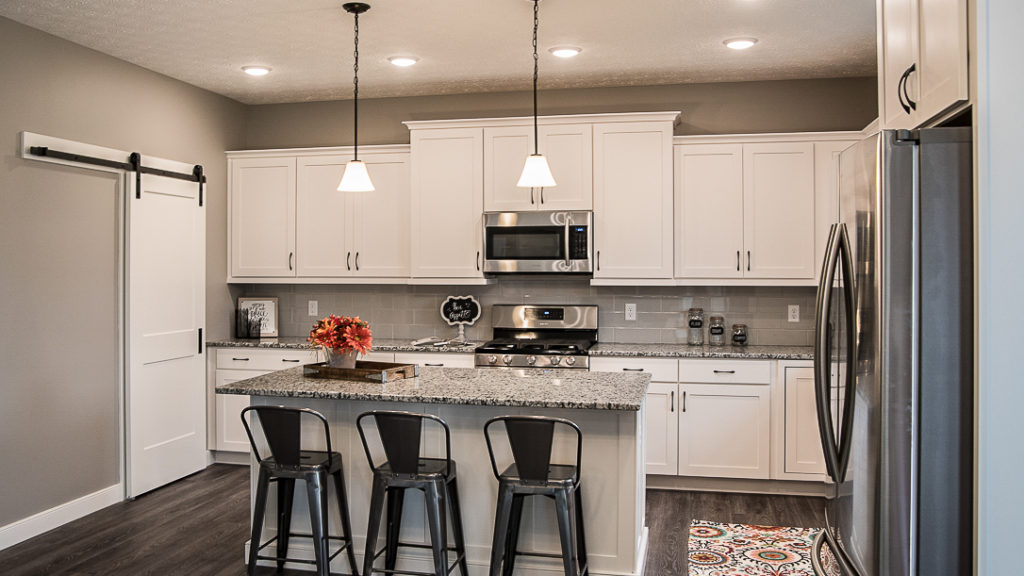 Kitchen of Arlington model features white cabinets and island, subway ceramic tile backsplash, and granite countertops