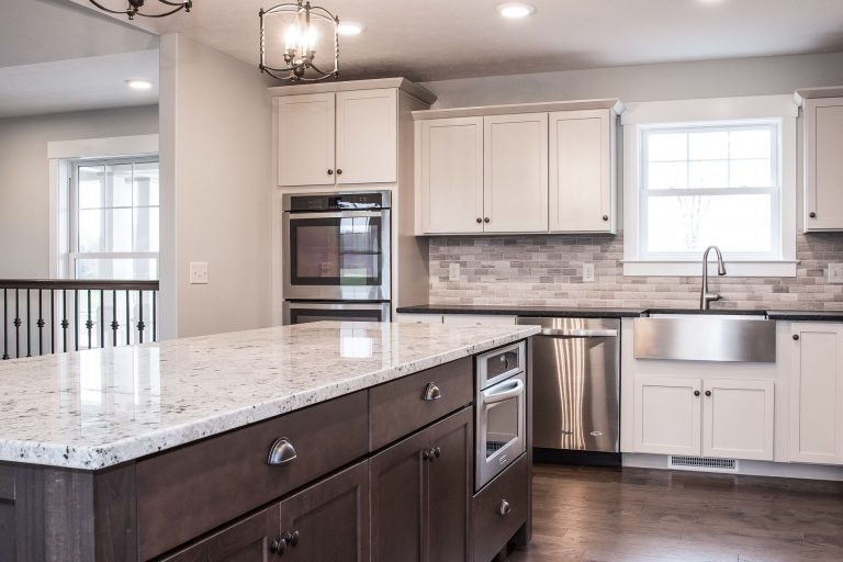 Latte Echelon Rossiter painted cabinets with Storm in island, New Kashmire White granite tops, Kraus apron-front KHF-200-30 sink