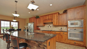 Kitchen of Excalibur model features rustic stained cabinets, granite countertops, and Sienna stone on the island
