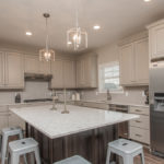 Kitchen of Windmill model features Wellborn painted cabinets in Pebble, LG Viatera Quartz in Aria, and decorative backsplash