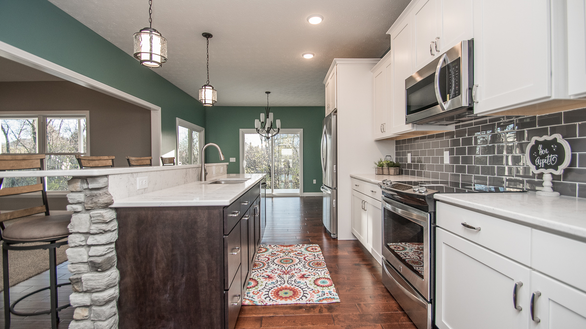 Kitchen of custom built home with white cabinets, quartz countertops and subway pattern backsplash