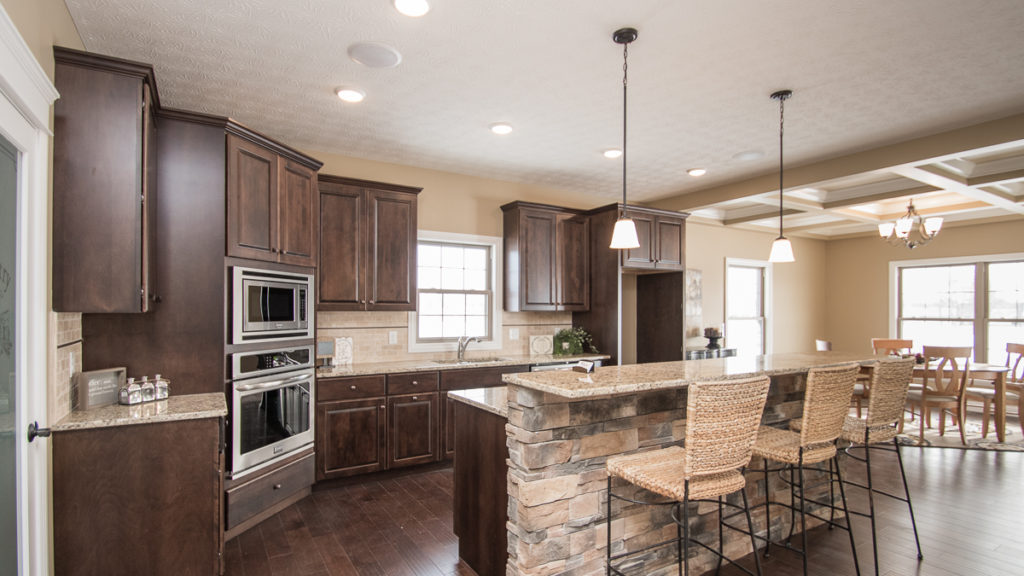 Kitchen of Excalibur model features dark stained cabinets, granite countertops, travertine backsplash and stone accents on island