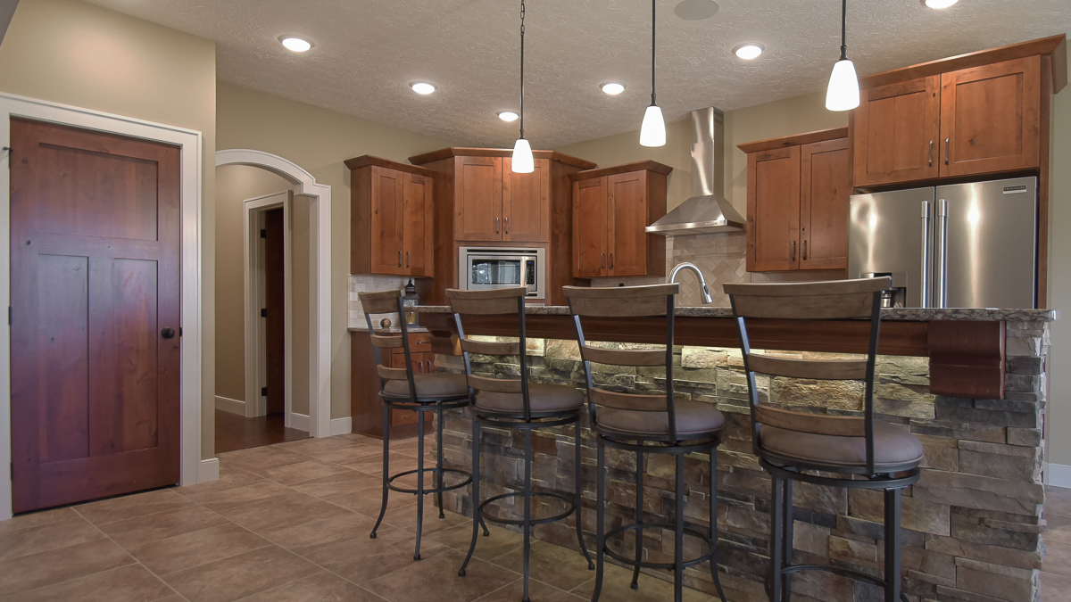 Kitchen of Barrington model features rustic Alder wood cabinets by Kemper, quartz countertops, stone accent on island, and travertine backsplash