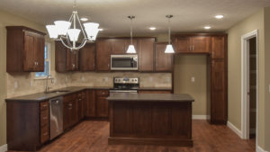 Kitchen of Avondale model features dark stained cabinets, leathered granite countertops and travertine staggered backsplash