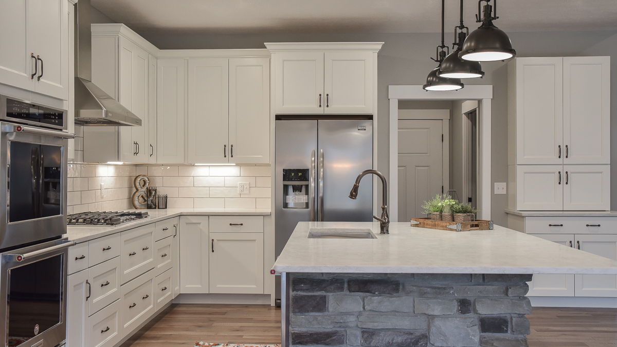 Kitchen of custom built home features white painted cabinets, quartz countertops, white subway backsplash, and stone accent on island