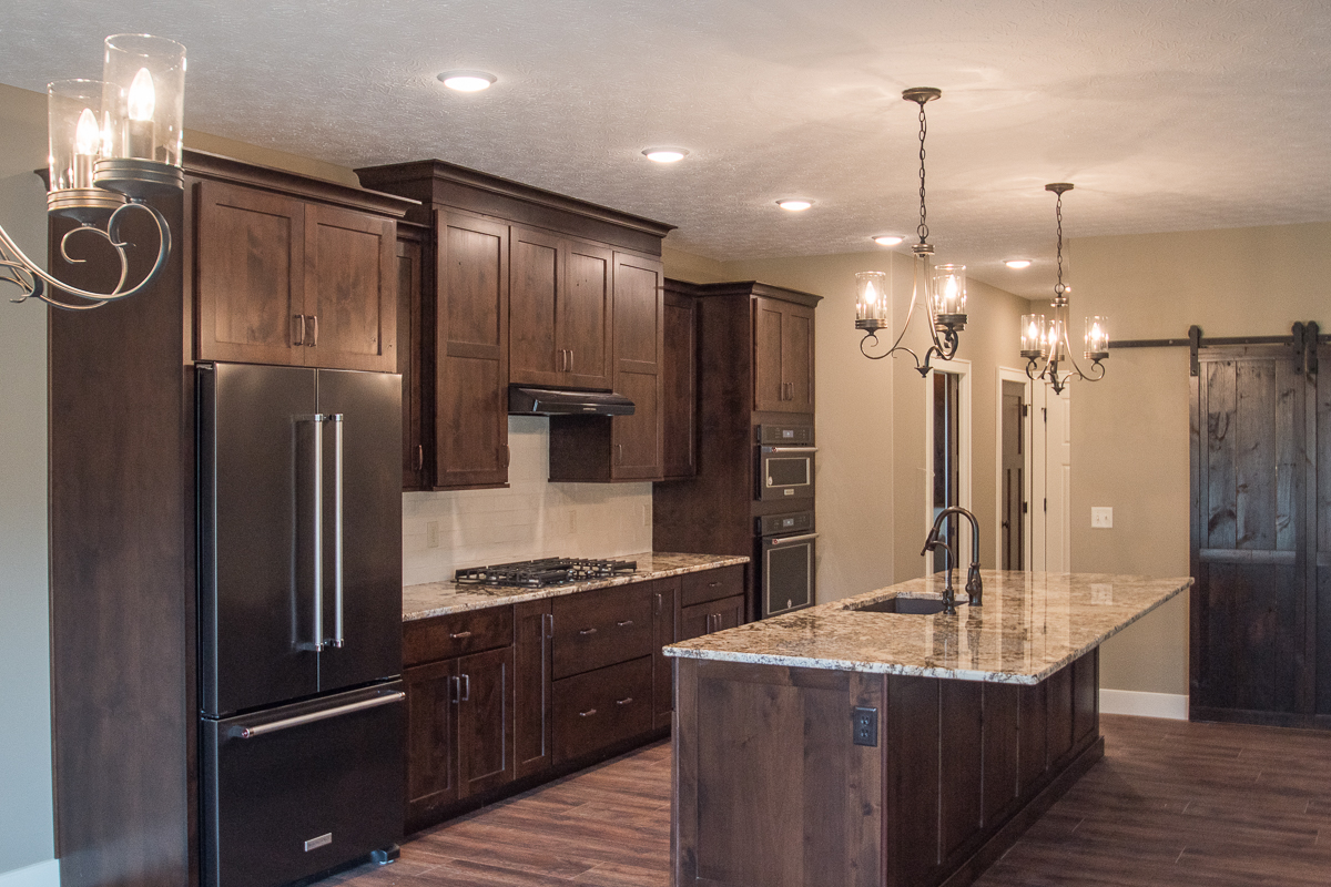 Kitchen of modified Glendale model features dark stained cabinets, granite countertops, and white ceramic subway pattern backsplash