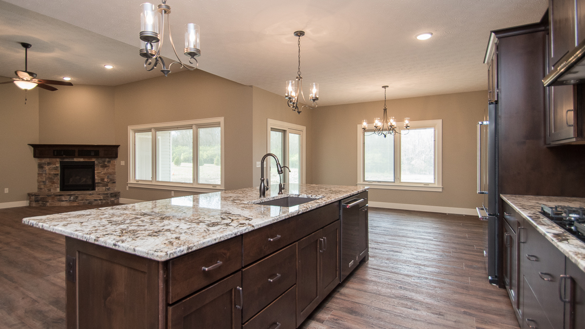 Kitchen of Glendale modified model features dark stained cabinets, and granite countertops