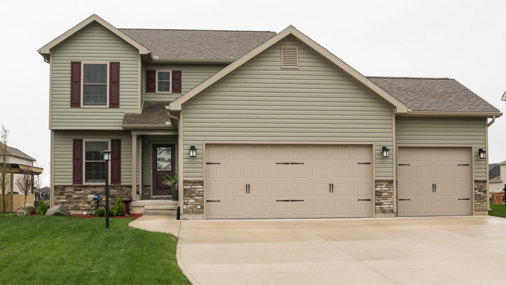 """Saratoga Model with Sagewood Stack Ledge stone, double 5"""" dutchlap vinyl siding in cypress built in Edgewater"""