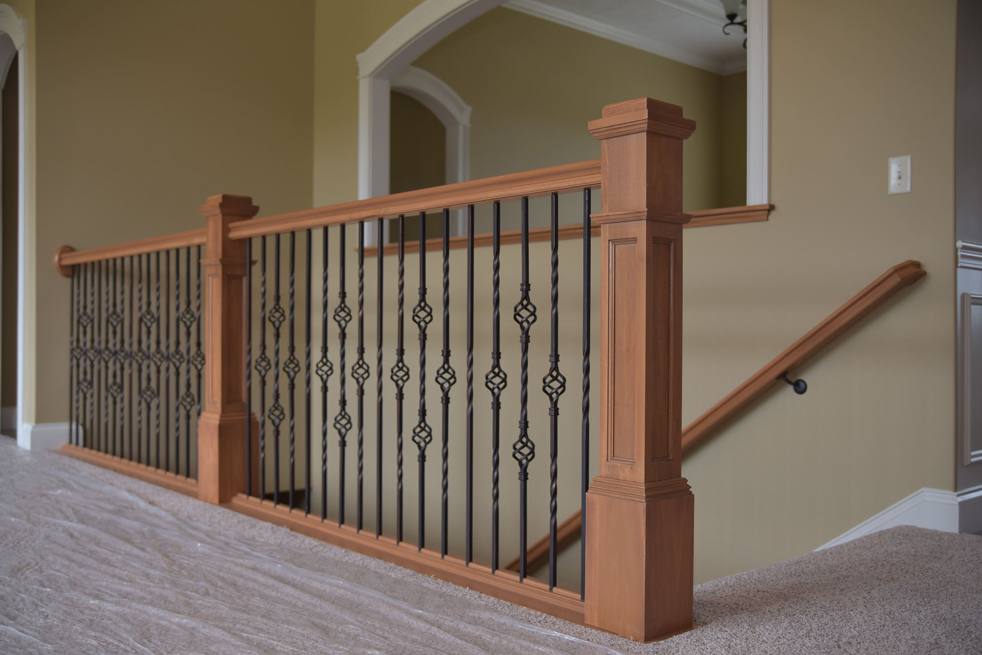 Stained railings & stained flat-panel box newels, Oil Rubbed Bronze balusters: single twist + single basket + double basket + single basket + repeat