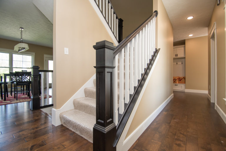 Stained railings and flat-panel box newel posts, painted skirtboards, painted square-chamfer balusters