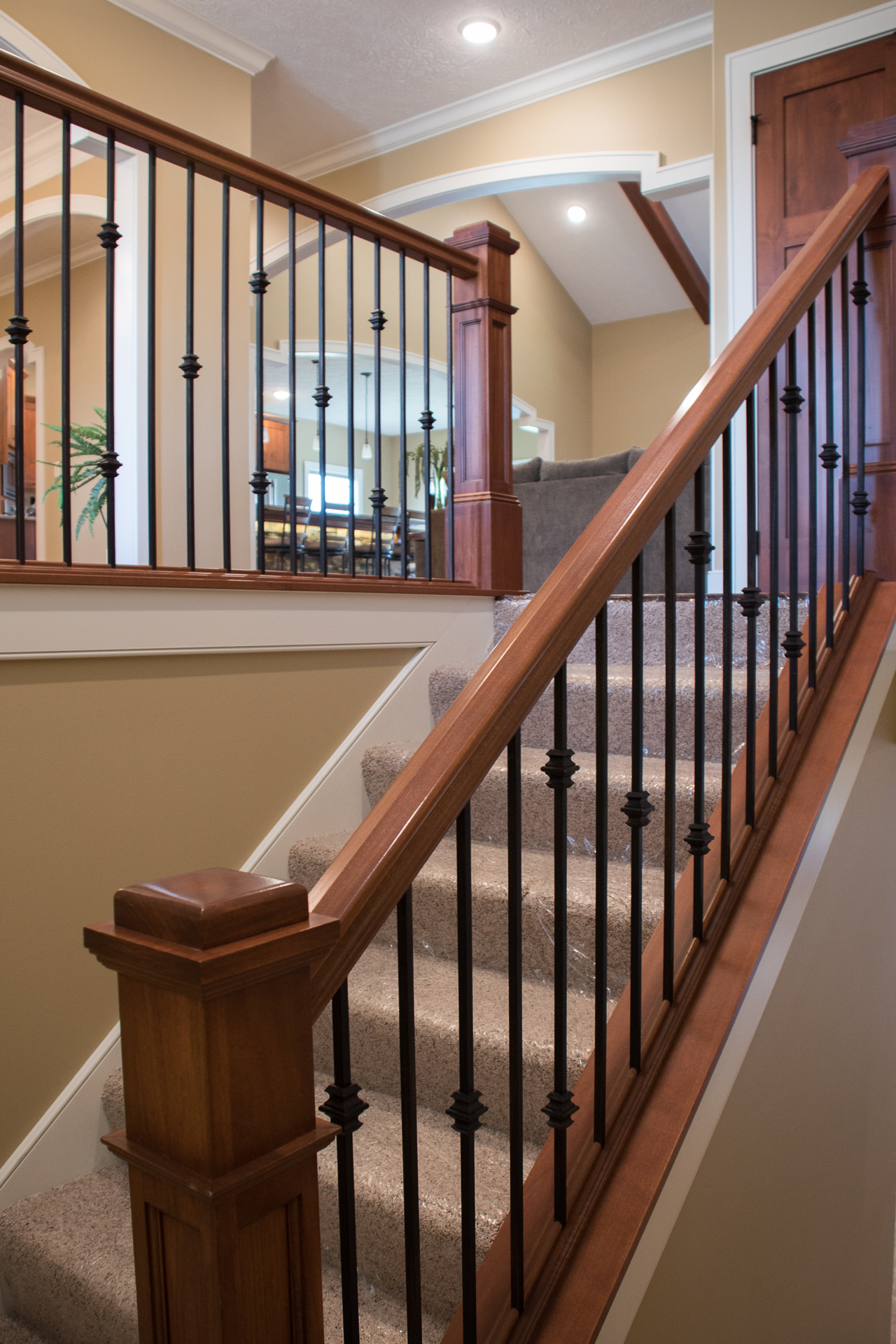 Stained newel posts & railings, painted skirtboards and knuckles-plain/double/plain/single iron balusters