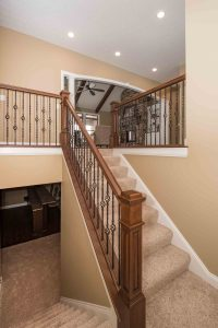 Stained handrail and box newels with oil rubbed bronze iron ballusters: double twist + single-basket + double-basket + single-basket pattern