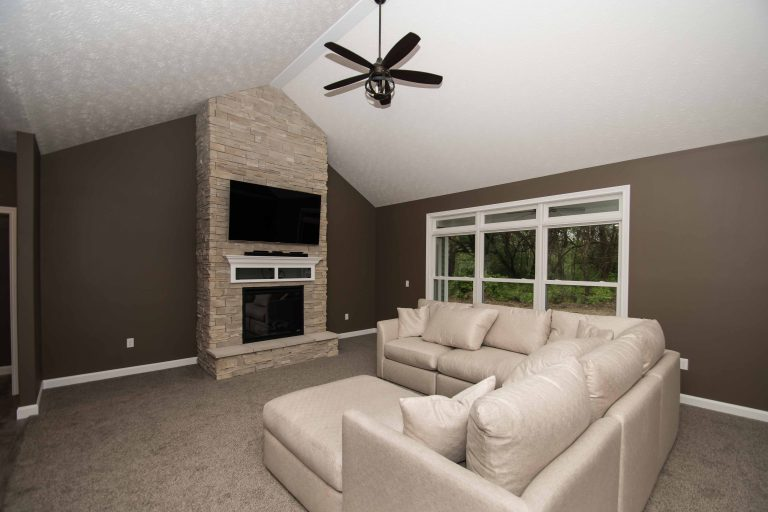 Great room of Excalibur model features floor to ceiling fireplace in Arizona Dry Stack stone