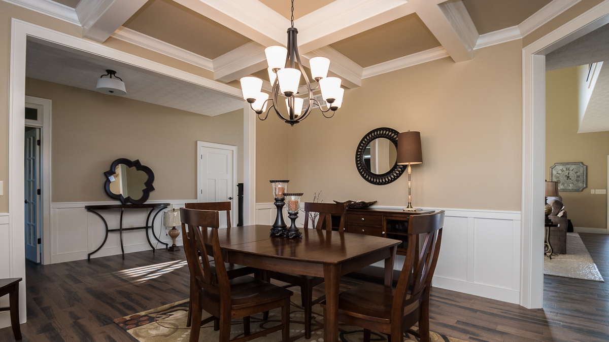 Dining room in this Berkshire model features coffered ceilings and wainscotting