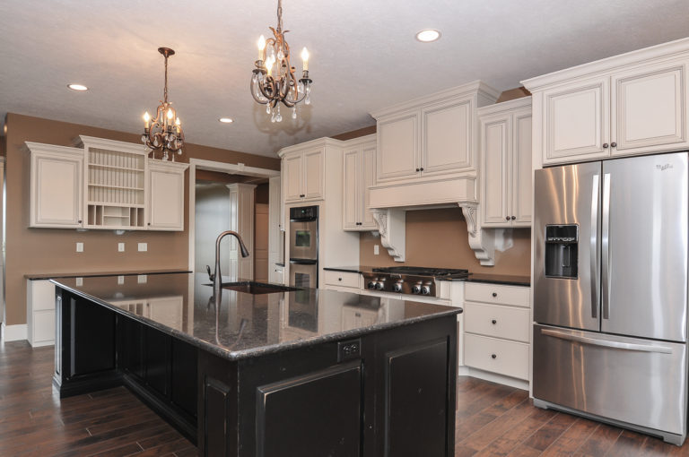 Custom kitchen features painted cabinets and granite countertops