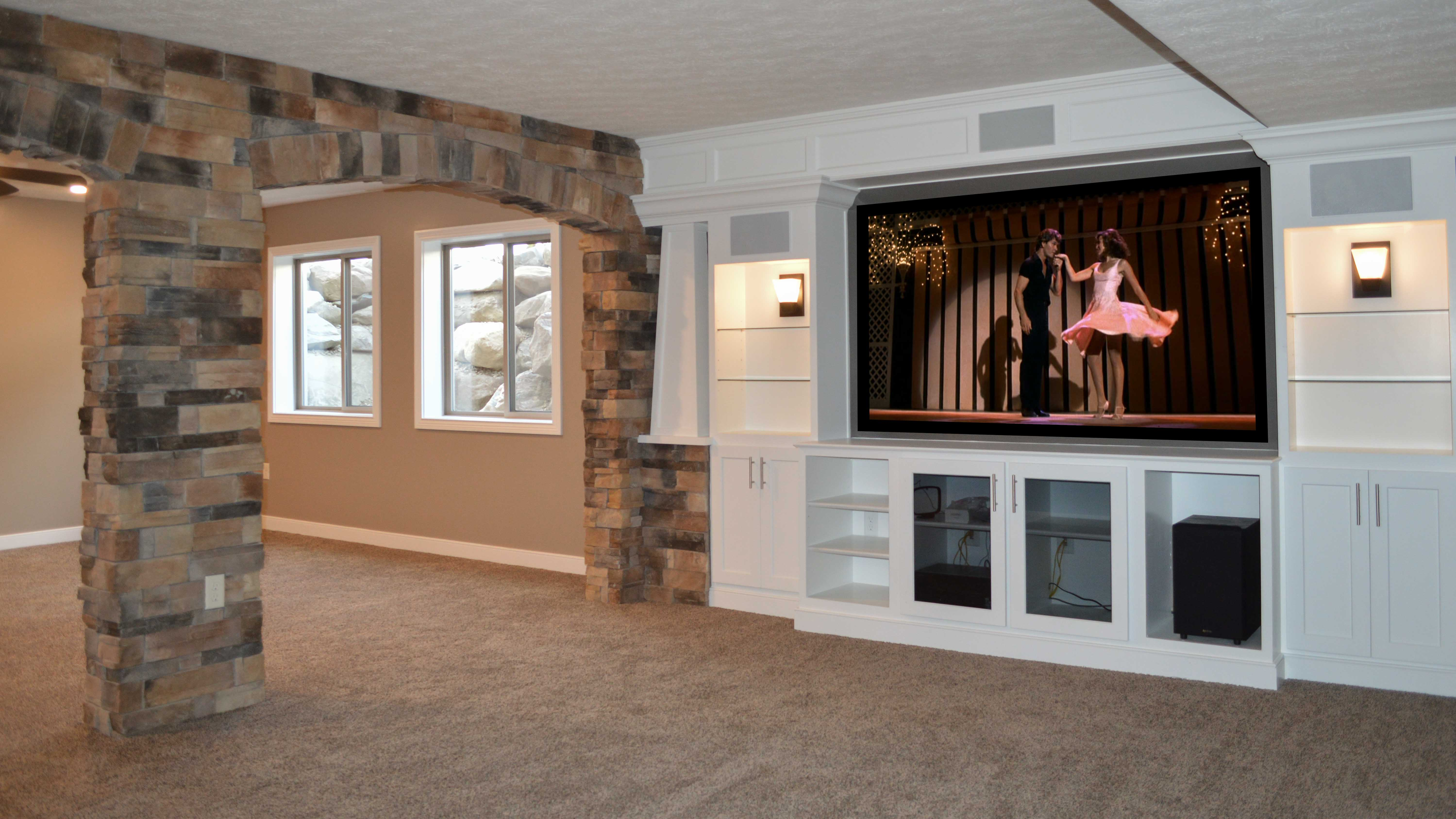 Theater room with stone accented walls and custom built-ins