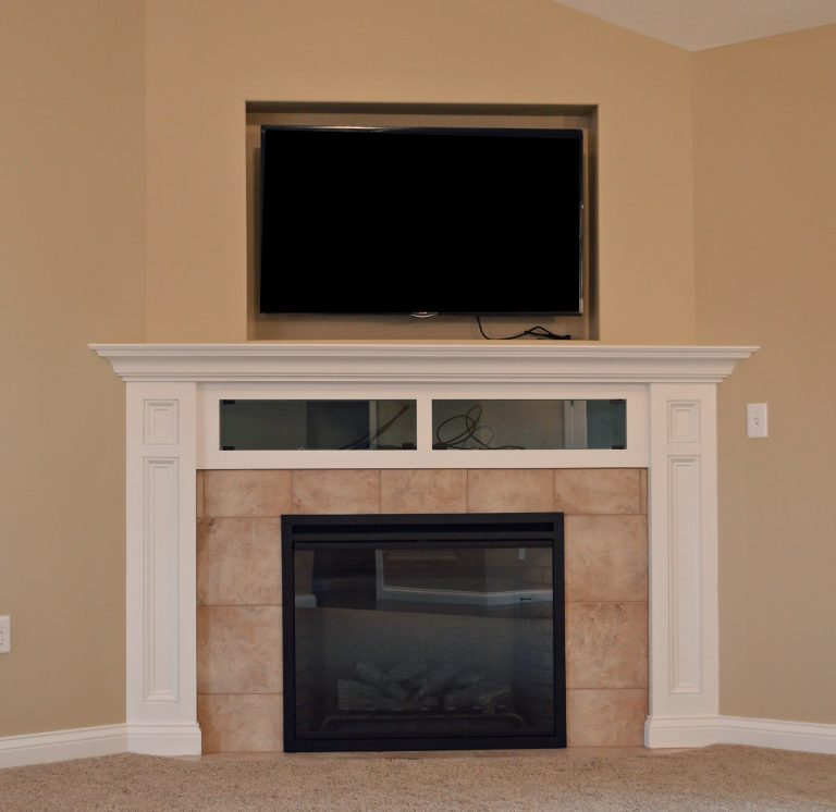 Corner fireplace with ceramic tile surround and painted wood trim. Glass-door component boxes