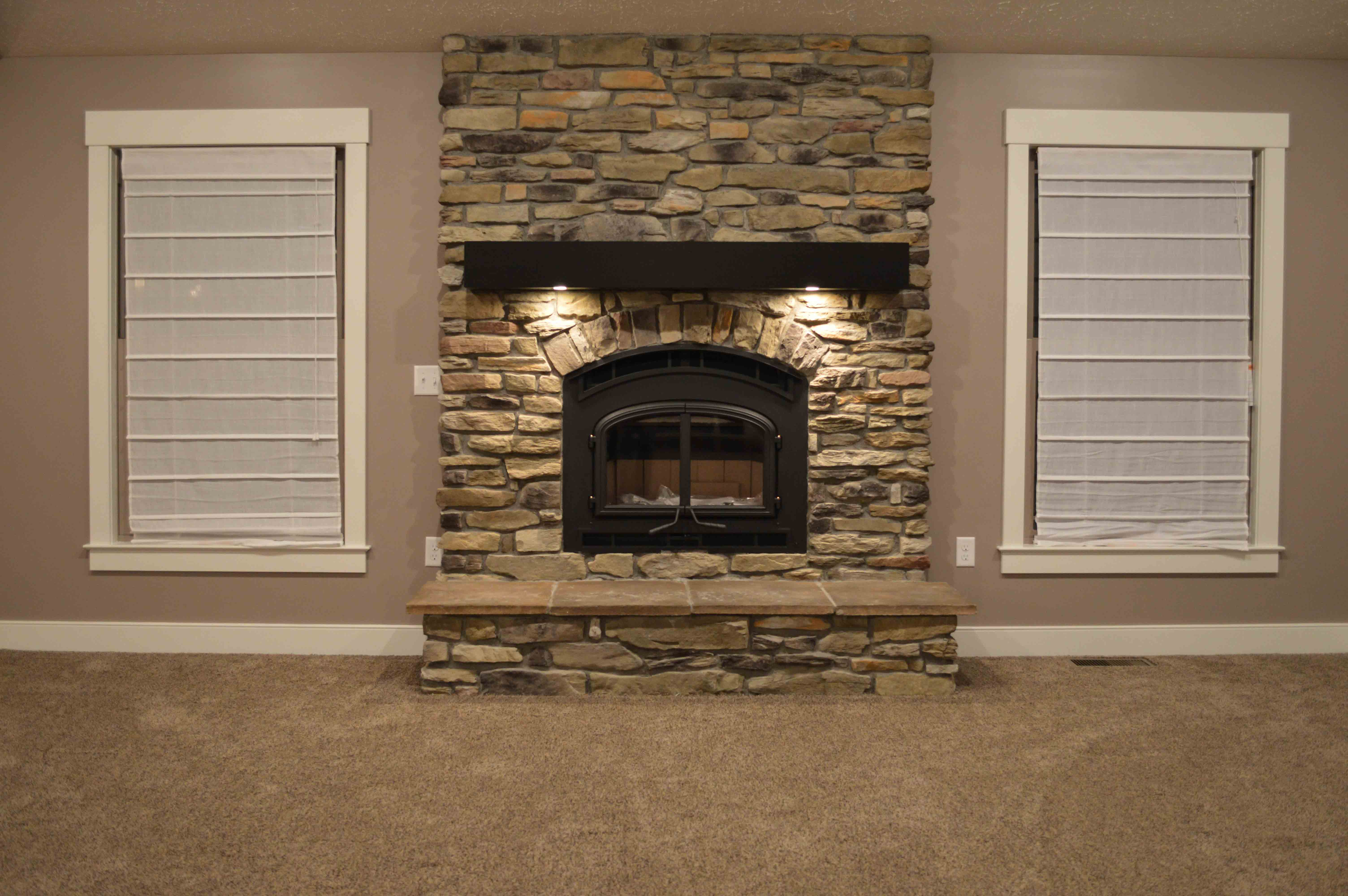 Wood burning fireplace with Sagewood Ledgestone and raised hearth. Mantle features accent lights