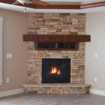 Corner gas fireplace with Tan Weather Ledge stone, hand-hewed wood beam for mantel and component box