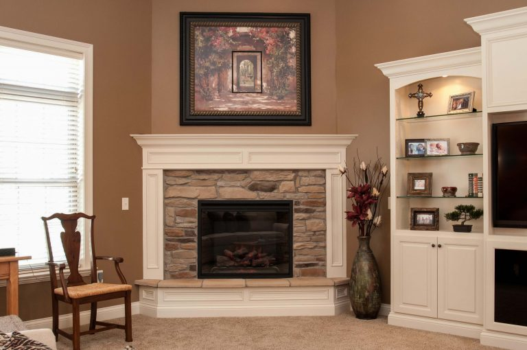 Electric corner fireplace with Natural Blend Ledgestone and painted wood surrounding trim - with raised hearth