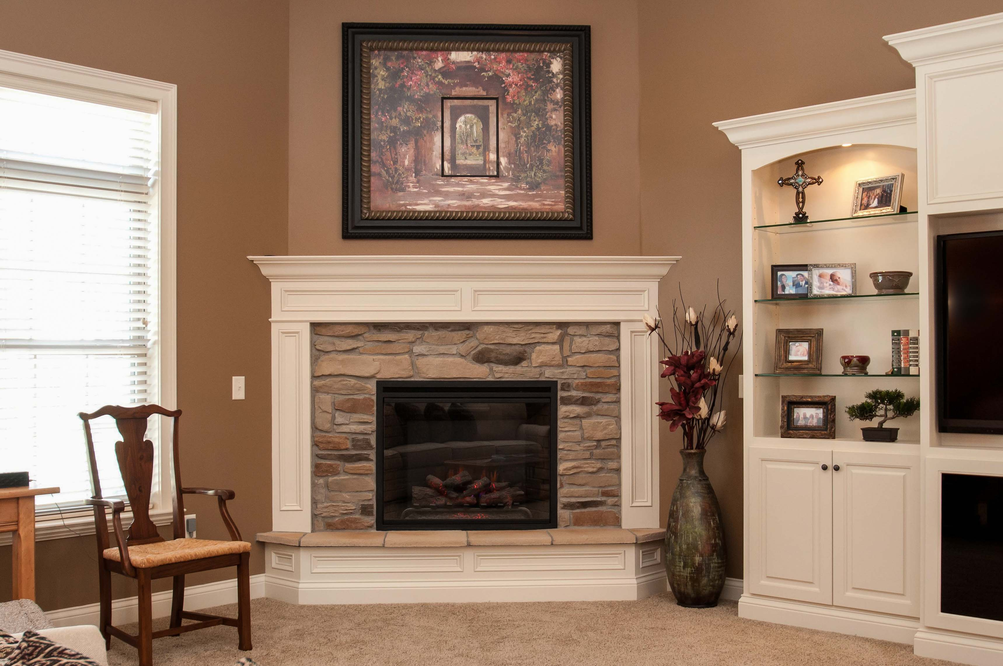 Electric Corner Fireplace With Natural Blend Ledgestone And Painted Wood Surrounding Trim Raised Hearth