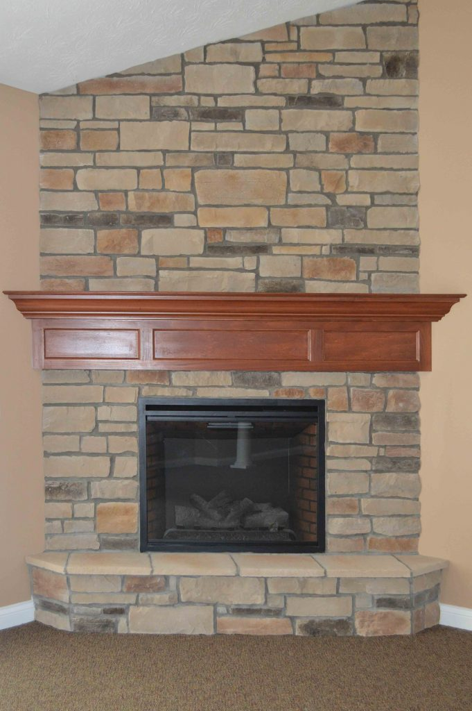 Corner fireplace with Natural Blend Weather Ledge stone, raised hearth and stained wood mantle