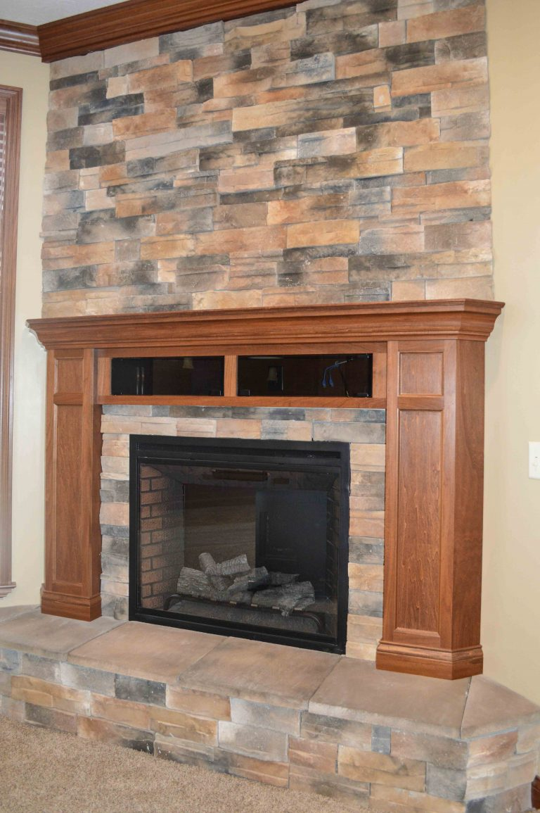 Corner fireplace with Sienna stone, raised hearth and glass-doors component boxes in stained wood mantle