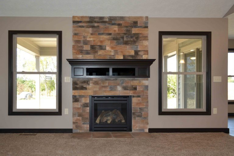 Gas fireplace with Sienna stone and glass-door component boxes in stained wood mantle