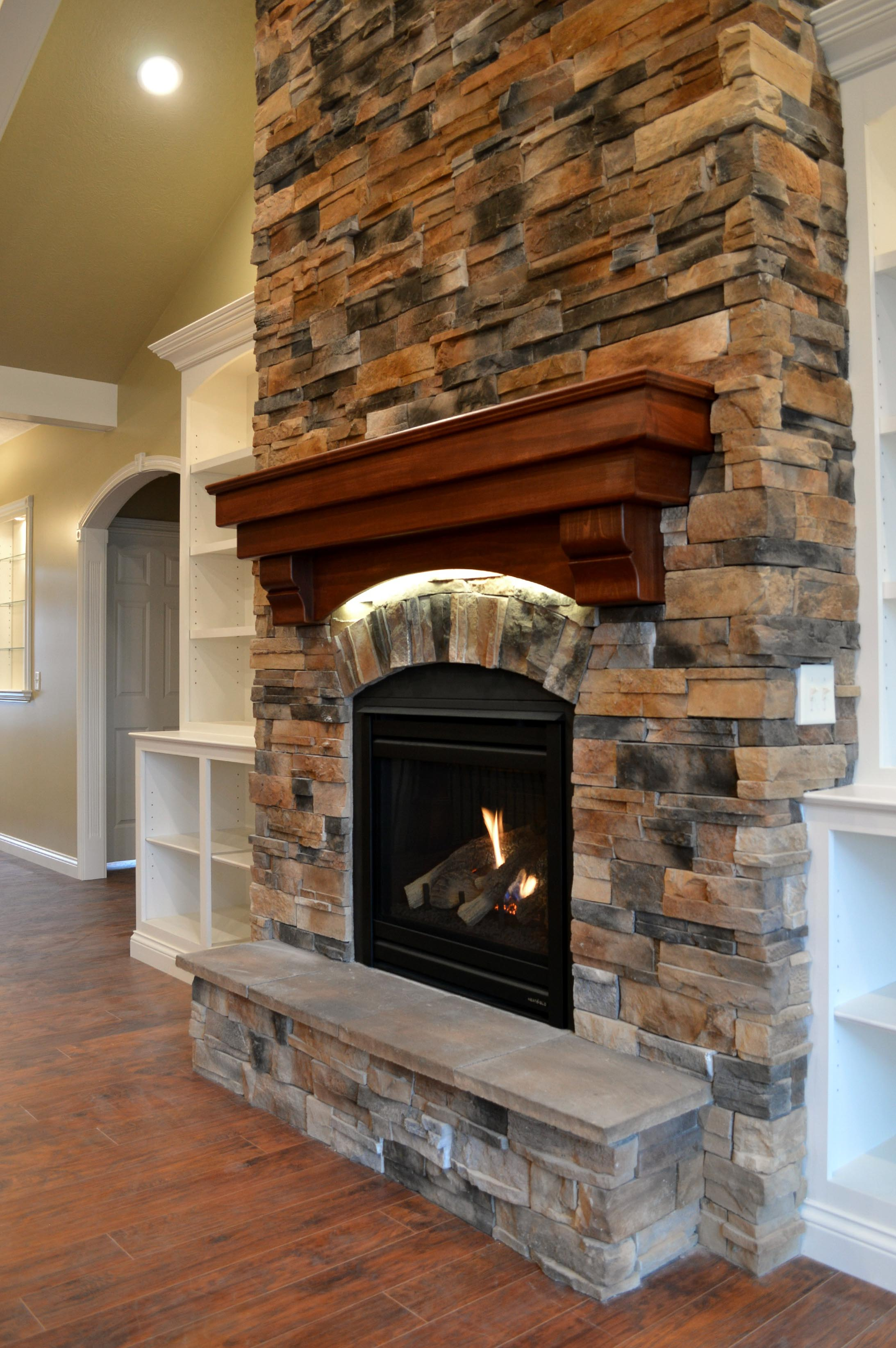 Gas fireplace with Sienna Dry Stack stone, raised hearth and accent light under stained wood mantle