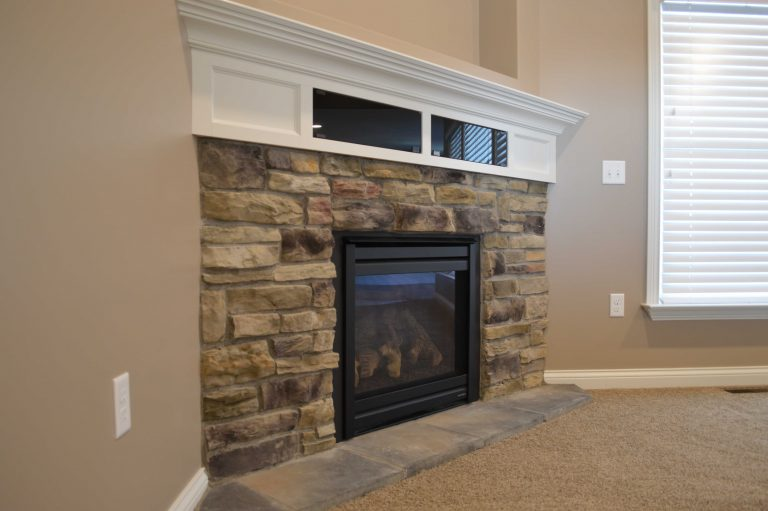 Corner gas fireplace with Sagewood Stack Ledge stone and glass-door component boxes in mantle