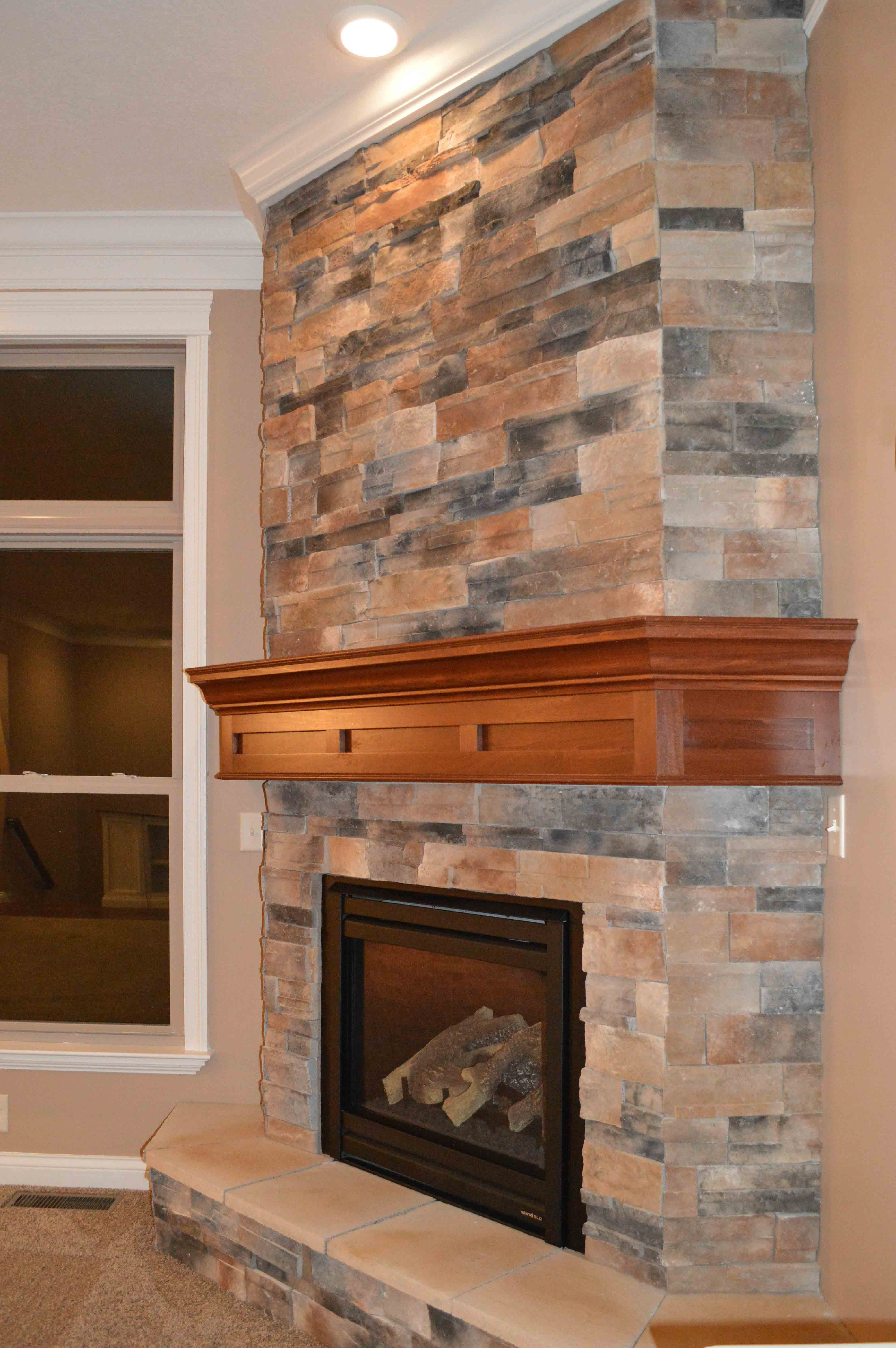 Gas corner fireplace with Sienna Dry Stack stone and raised hearth