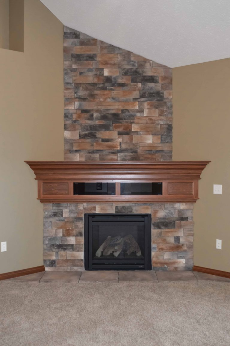 Gas Corner fireplace with Sienna Dry Stack stone and glass-door component box in stained mantel
