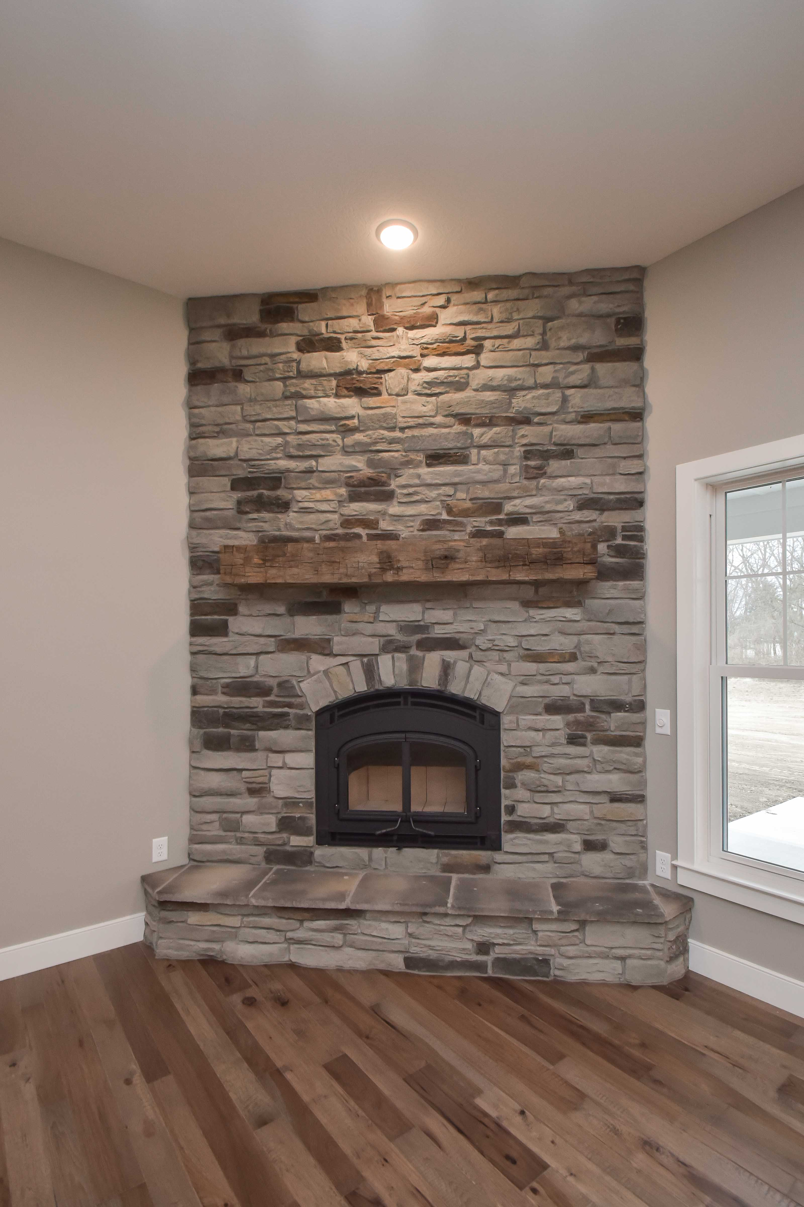 Wood burning fireplace (Quadra-Fire 7100-Mission Hill Black front), raised hearth, Steinhaus Stack Ledge stone