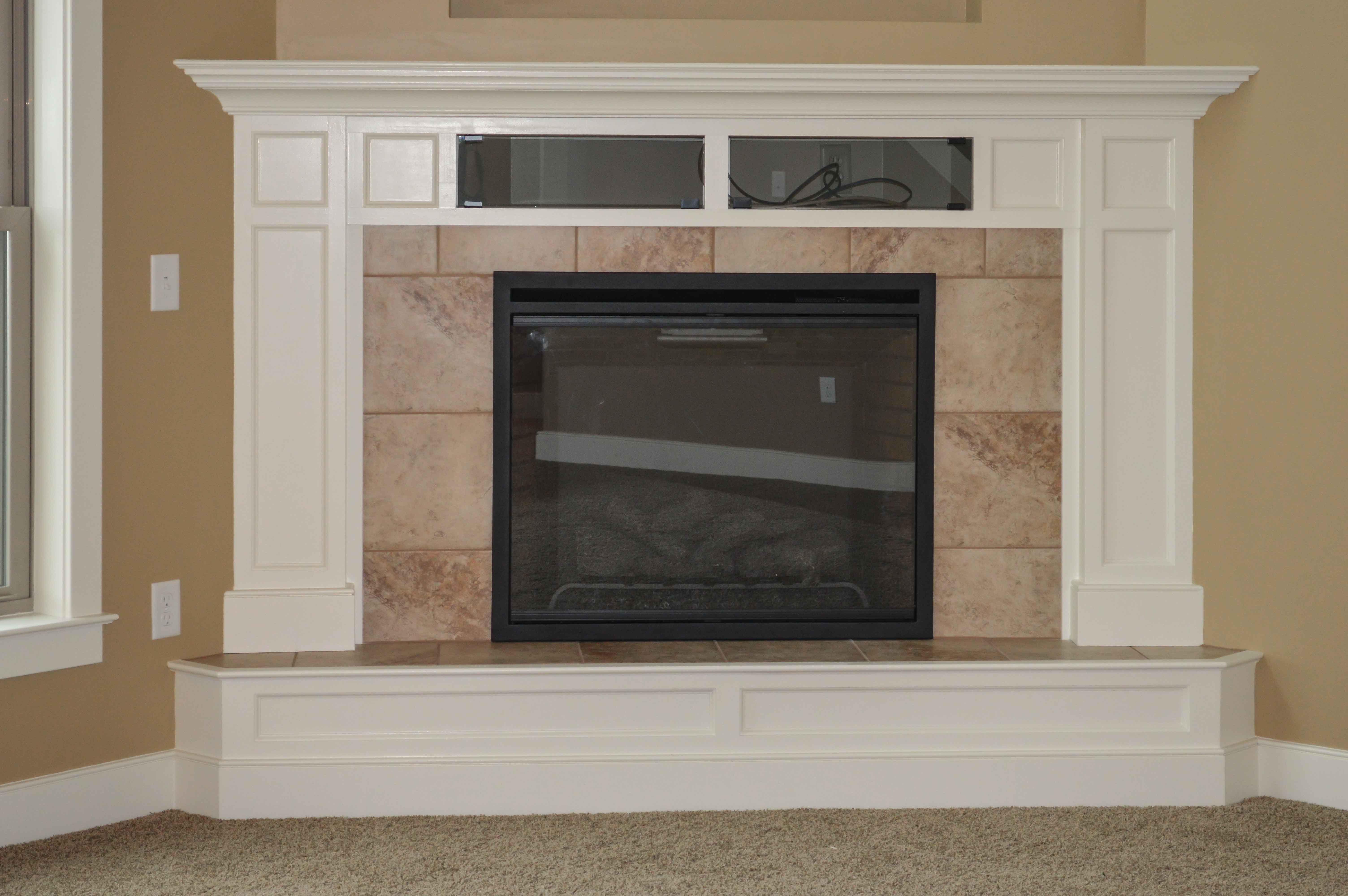 Corner fireplace with raised hearth and ceramic tile surround. Glass door component boxes in mantle