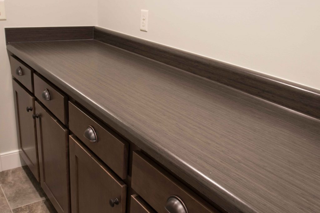 Wall-to-wall lower cabinets with laminate top perfect for folding area and plenty of storage!