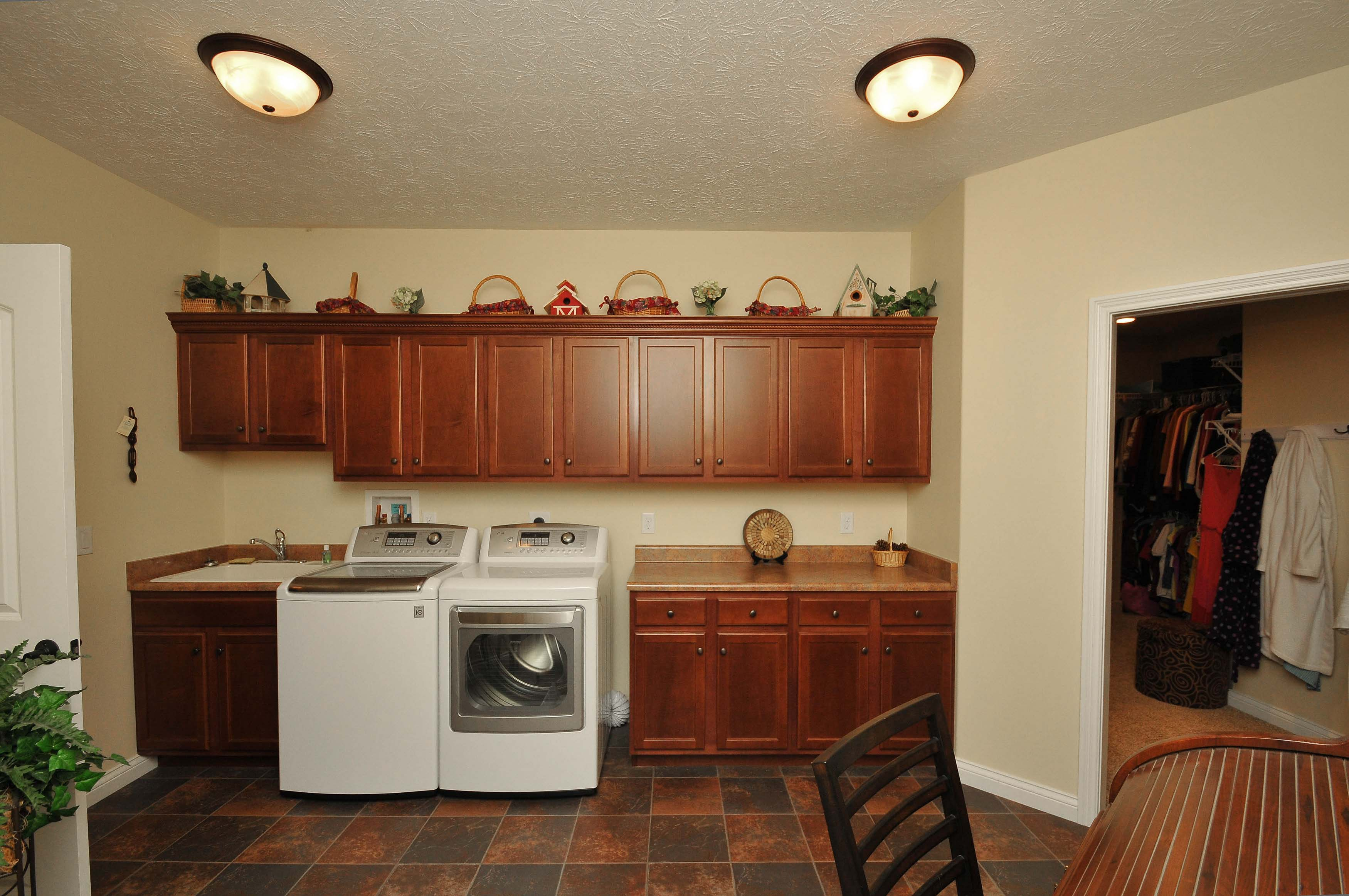 Extra large laundry room offers plenty of storage with upper and lower cabinets, a drop in utility sink and folding space!