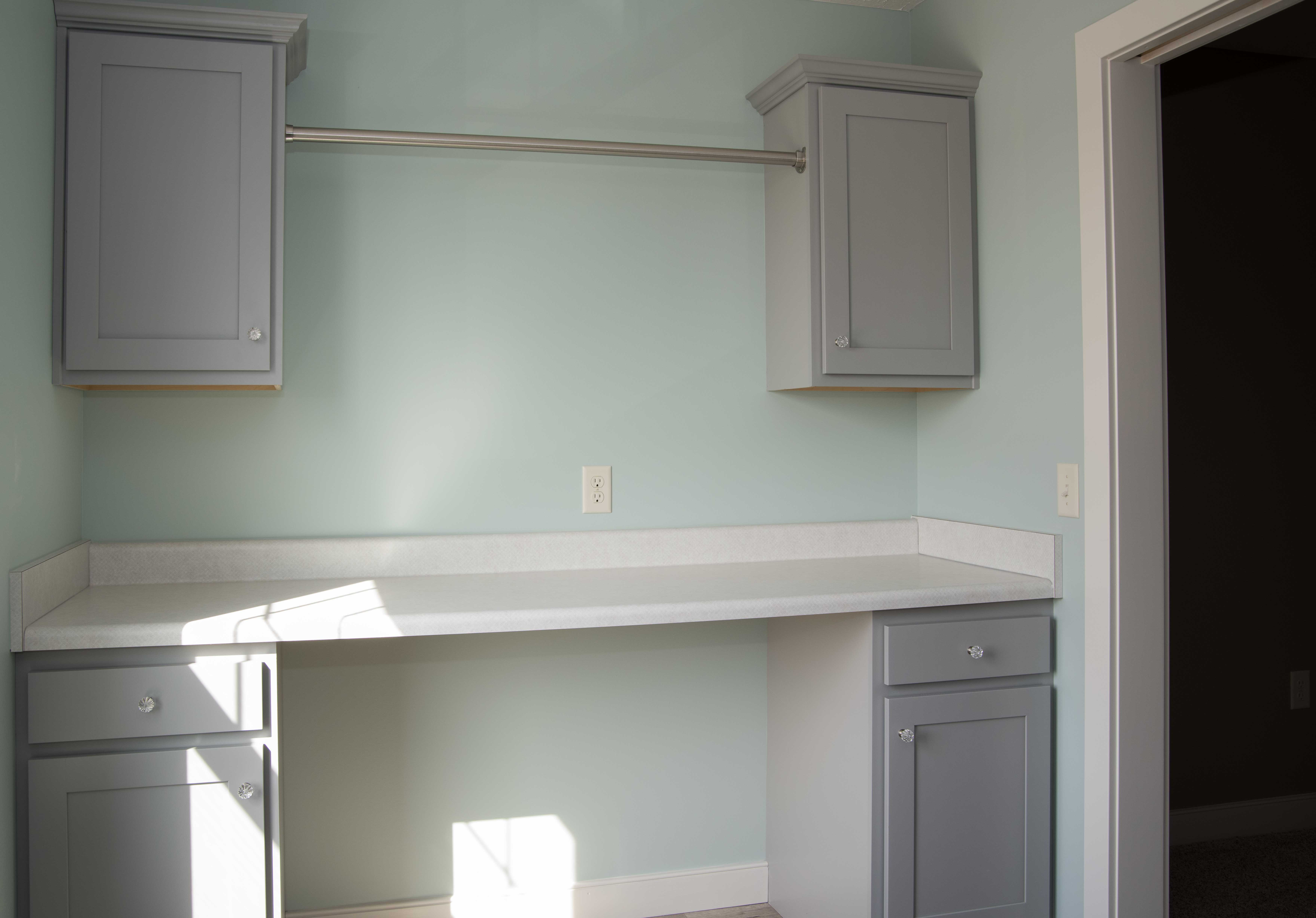 Hanging rod between upper cabinets and wall-to-wall folding area