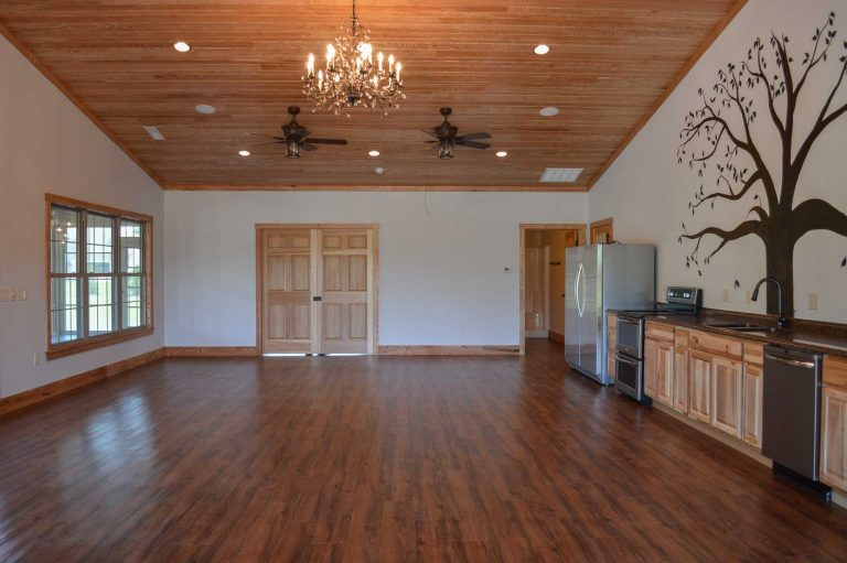 Large open room for gathering with tongue & groove pine ceiling, and a fully functional kitchen