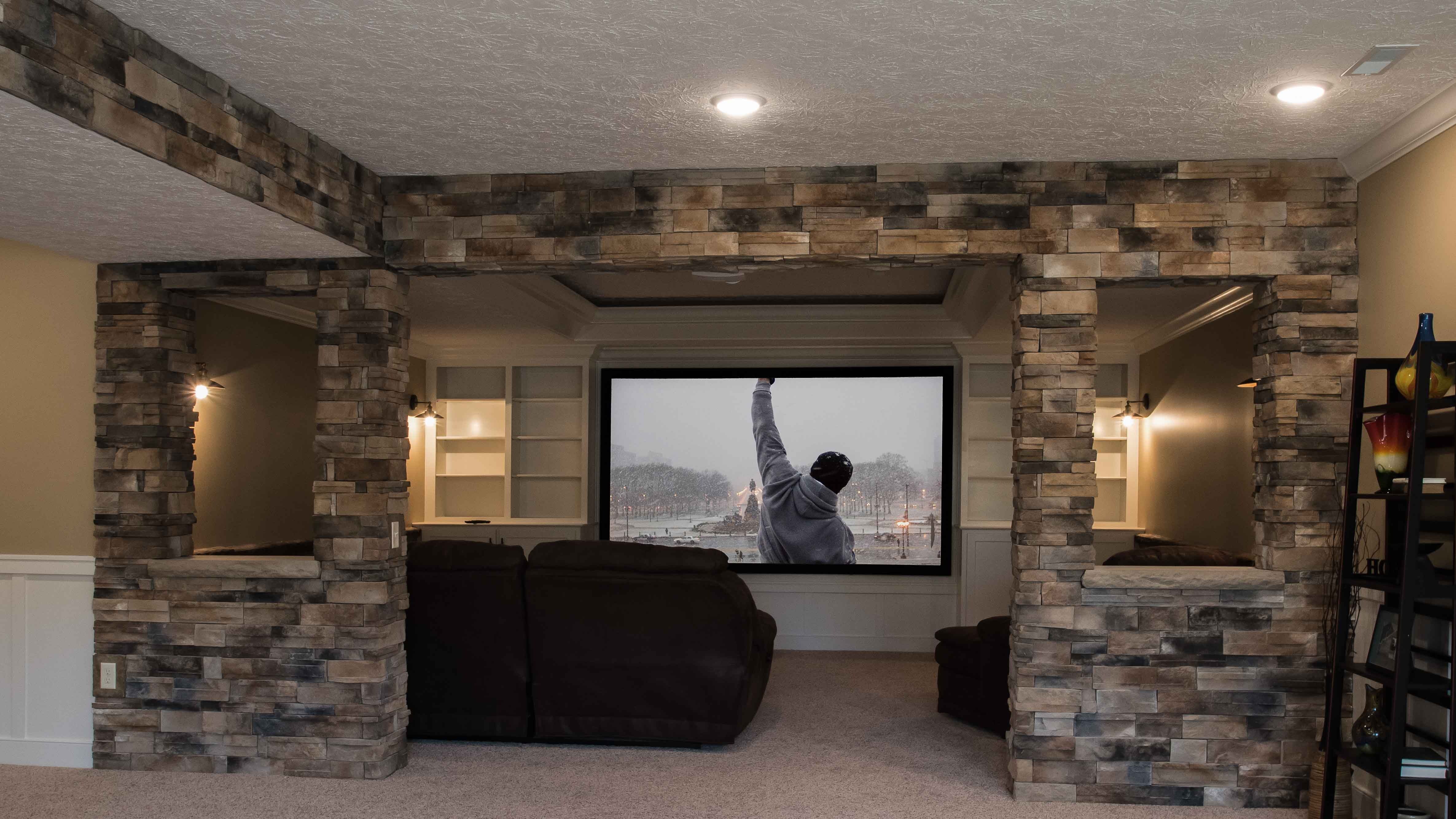 Barrington model theater room features Sienna Dry Stack stone, custom built ins, and trey ceiling