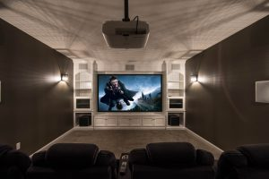 This theater room features custom built ins and in-wall speakers