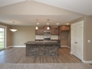 Island in kitchen of Fenway model feautures granite and stone accent on front