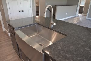 Granite countertops with stainless steel apron front sink and Moen Arbor faucet