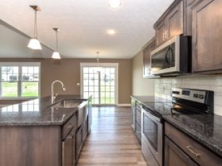 Kitchen in the Fenway Model features Koch Express Windsor 15 Rustic Birch Stone cabinets with soft-close drawers and doors, granite countertops, and subway tiled backsplash